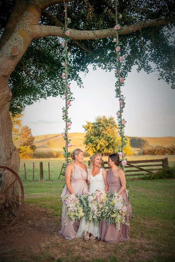 Bride and her girls for a lovely bridal party photoshoot next to a swing on a farm wedding