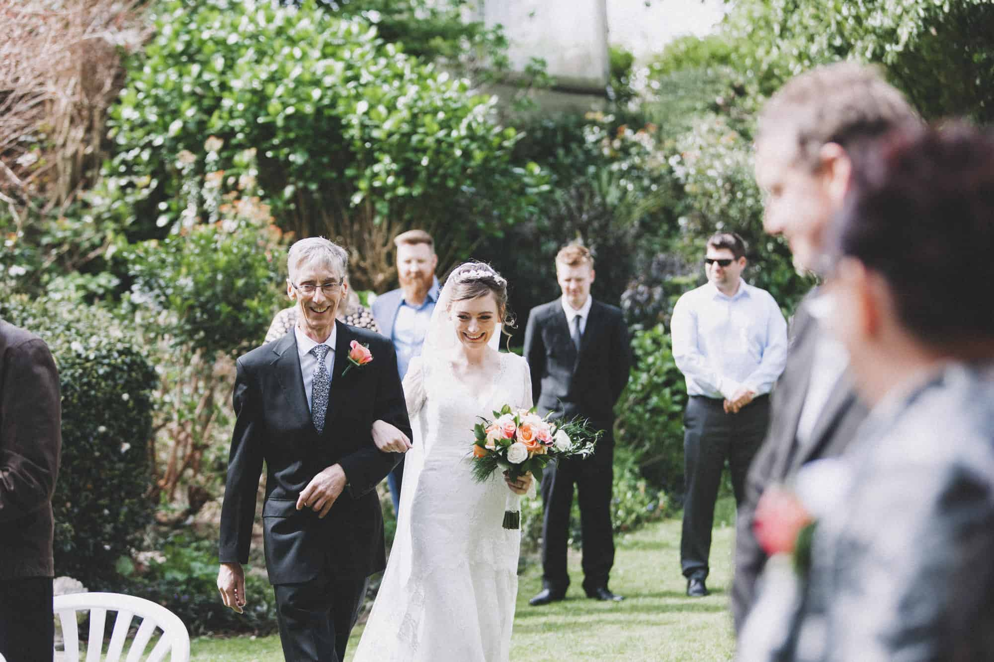 An intimate new zealand wedding photo of bride and father walking down the aisle