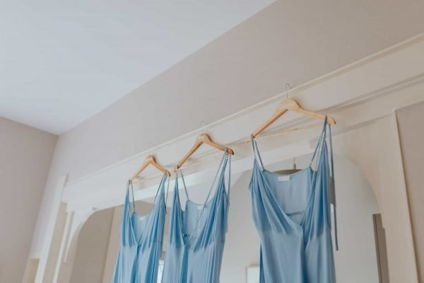 Soft blue bridesmaid wedding dresses hanging up at getting ready
