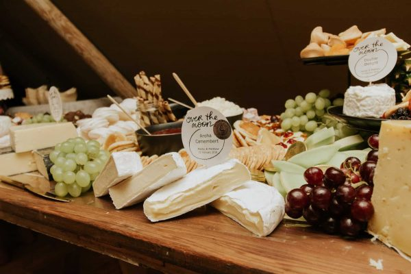 A stunning wedding reception idea of a cheese board full of goodies for wedding guests