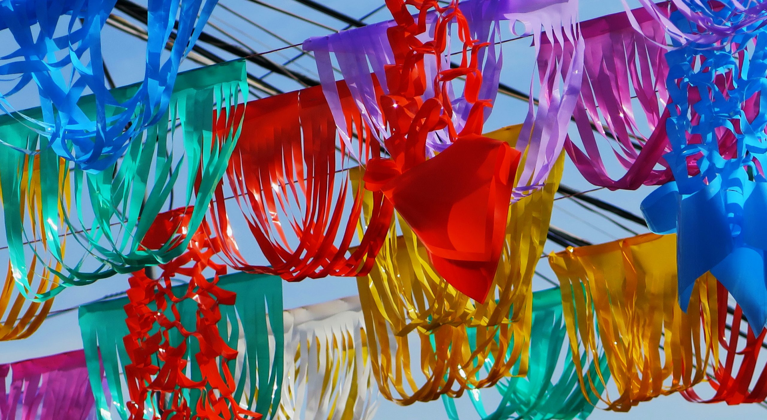 Very colorful streamers and decorations hanging up on lines