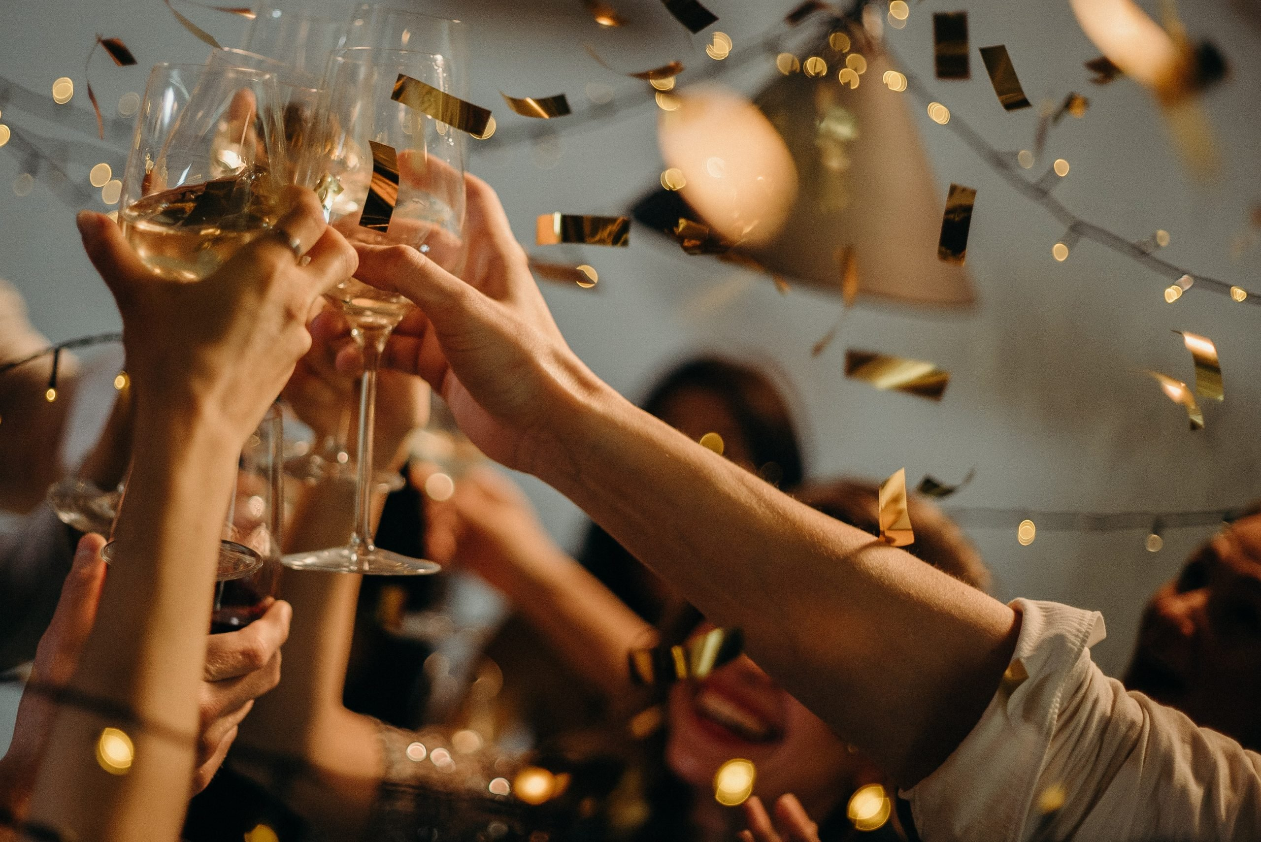 People cheering with wine glasses with gold confetti in the air